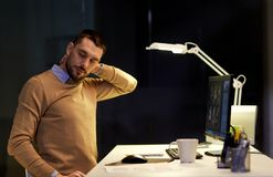 Tired man having neck ache working at night office. Business, deadline and health concept - tired man having neckache working at night office Royalty Free Stock Image