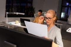 Businesswoman with papers working at night office. Business, deadline and technology concept - businesswoman with papers and computer working at night office stock photography