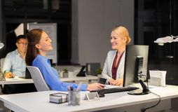 Businesswomen with smartphone late at night office stock images