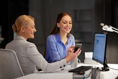 Businesswomen with smartphone late at night office royalty free stock image