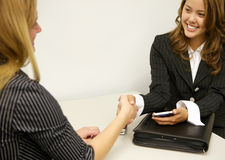 Business Deal. A business deal between two women concluding with a handshake royalty free stock photos
