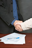 Business deal. Business deal between business man and client with the signed document on the table Stock Images