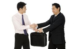 Business Deal. Two young asian businessmen complete a business deal on white background Stock Photo