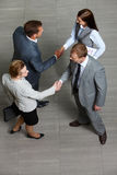 Business deal. Four business partners handshaking while striking deal royalty free stock photos
