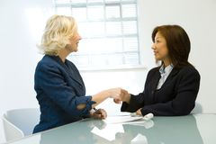 Business Deal. Two middle-aged businesswomen finalizing a business deal in an office Royalty Free Stock Image
