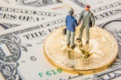 Business deal or agreement and success concept. Two miniature businessmen shaking hands while standing on bitcoin cryptocurrency a stock photos