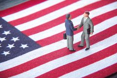 Business deal or agreement and success concept. Two miniature businessmen shaking hands while standing on USA american flag backgr stock images