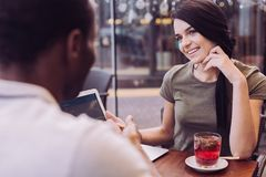 Young two colleagues talking about business. Business deal. Brunette appealing pretty women smiling while looking at men and touching her face Royalty Free Stock Images