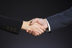 Business deal. Deal, business  handshake. Woman and man hand on a gray background Stock Photo
