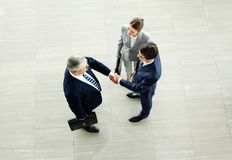 Business deal. Image of business partners handshaking after striking deal with smart women near by royalty free stock photo