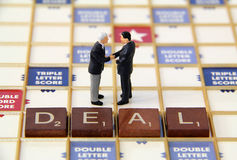 Business Deal. Two business men figurines closing a business deall Royalty Free Stock Image