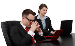 Business Decisions. Businessman thinking in front of his notebook near a young female colleague on their desk Stock Photo