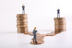 Business Decisions Concept. Miniature businessman pondering which path to take. Other businessmen stand over him on stacks of quarters Stock Photography