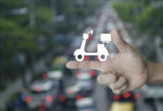 Business delivery service concept. Motor bike icon on finger over blur of rush hour with cars and road, Business delivery service concept Stock Photo