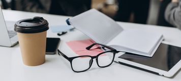 Business desk with a notebook, glasses, pen and tablet on white table royalty free stock images