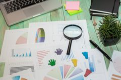 Looking at growth chart with magnifying glass. Graphs, charts an. Business Desktop. Looking at growth chart with magnifying glass. Graphs, charts and magnifying royalty free stock image