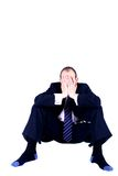 Business despair. A businessman experiencing despair with both hands covering his face, slumped on the floor, isolated on white background Stock Photos