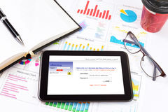 Business detail of a tablet lying on top of business charts and graphs. Stock Images