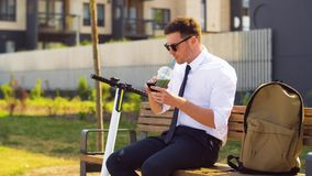 Businessman with smartphone drinking smoothie stock footage