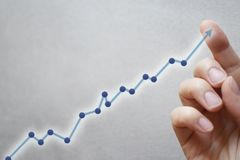 Finger touching blue arrow on graph stock images