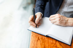 Business diary. Human hands with pen writing down ideas on blank page of notebook Royalty Free Stock Photo