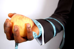 Business Diet - Apple. A black businessman holding a apple, tied with a tape measure royalty free stock image