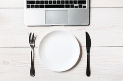 Business or diet concept, workplace with laptop and empty plate with cutlery. Mockup for lunch in office. Business or diet concept, workplace with laptop and Royalty Free Stock Photos