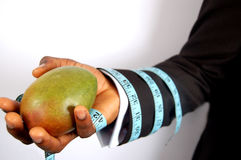 Business Diet - Mango. A black businessman holding a mango, tied with a tape measure royalty free stock photo