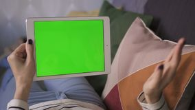 Business digital asian woman holding a mockup green screen tablet, on couch at home stock video footage