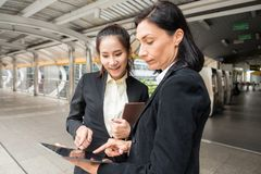 Business discuss and meeting in city. American businesswoman manager and her underling teammate look at project plan on digital tablet with copy space for text Stock Photos