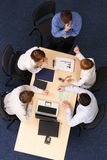 Business discussion. An over-head view of young executives sitting at a table, having a meeting royalty free stock images