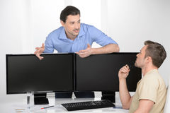 Business discussion. Two young businessmen talking about busines. S while one of them leaning on the computer monitors Royalty Free Stock Photo