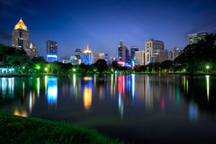 Business district cityscape from a park with twilight time from lumpini park Royalty Free Stock Images
