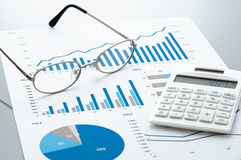 Business document, glasses, and calculator on gray reflection ba. Many graphs and charts. Concept image of data reviewing royalty free stock photography