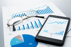 Business document, glasses and smartphone on gray reflection background. Many graphs and charts. Concept image of data reviewing stock images