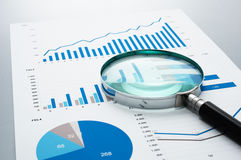 Business document and magnifying glass on gray reflection background. Many graphs and charts. Concept image of data reviewing stock images