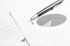Business document with pie graph, focus to the text Sale. Monochrome image of ballpoint pen lying on a business document with pie graph, focus to the text Sale Stock Image