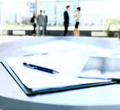 Business document in touchpad lying on the desk, office workers interacting in the background Stock Photo