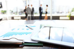 Business document in touchpad lying on the desk, office workers interacting in the background Royalty Free Stock Photo