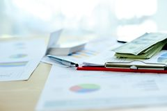 Business documents, financial graphs, and graphs on the work desk. Blocked with multiple dollar deposits. Is the goal royalty free stock image
