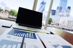 Business documents on office table with pen and digital tablet. As work space business concept with london city blurred background Royalty Free Stock Photo