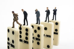 Business Dominoes. Miniature businessmen standing on upright dominoes Royalty Free Stock Photos