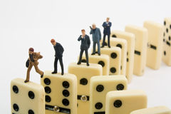 Business Dominoes. Miniature businessmen standing on upright dominoes Stock Photography
