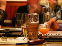 Business drinking. Half empty beer glasses on table and blurred faces and men's hands around and in the background Royalty Free Stock Image