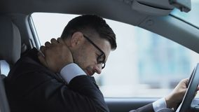 Business driver massaging numb neck sitting on driver seat, sedentary lifestyle