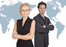 Business duet next to world map. Businessman and businesswoman standing Royalty Free Stock Images