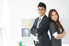 Business duo. Portrait of an enthusiastic business duo standing back to back royalty free stock photography