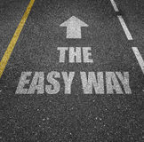 Business the easy way. Text 'the easy way' inscribed in uppercase white (gray) letters on a tarmacadam road with a bold arrow pointing the way forward for stock photography