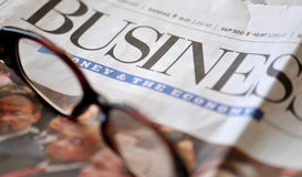 Business and the economy. Business section of a newspaper and glasses stock images