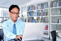 Business Education. A businessman or a lecturer or post graduate student (Master Degree) using laptop for work or doing a research on a laptop inside a modern stock images